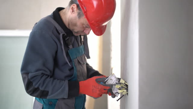 electrician installing light switch. - repairman stock videos & royalty-free footage