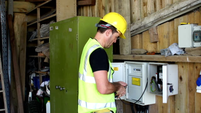 electrician / repair man working with cables at fuse box - fuse box stock videos and b-roll footage