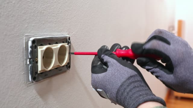 electrician using a screwdriver to take off the electrical plug - installing stock videos and b-roll footage