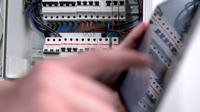 electrician using digital tablet in front open fuse box, close-up - electrician stock videos & royalty-free footage
