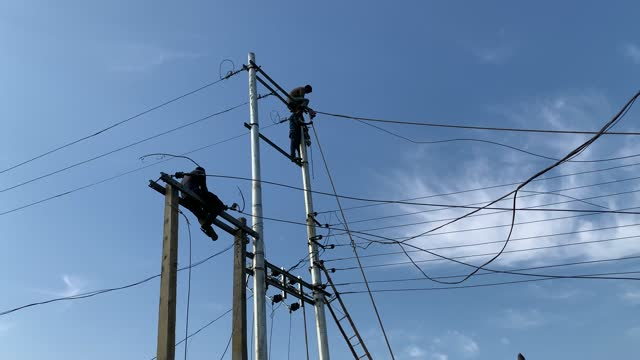 electricians work on the top of an electric poll on january 31, 2021 in barpeta, india. india's power consumption grew by 6.1% to 107.3 billion units... - power line stock videos & royalty-free footage