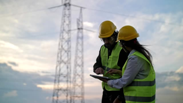 electricity engineers working on the field near a high voltage line with a clear blue sky and sun rays behind them. - electricity pylon stock videos & royalty-free footage