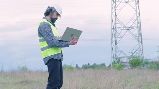 elektrizitätsingenieure arbeiten auf dem feld in der nähe einer hochspannungsleitung mit einem klaren blauen himmel und sonnenstrahlen hinter ihnen. teamarbeit. - coworker stock-videos und b-roll-filmmaterial