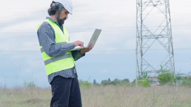 elektrizitätsingenieure arbeiten auf dem feld in der nähe einer hochspannungsleitung mit einem klaren blauen himmel und sonnenstrahlen hinter ihnen. teamarbeit. - bürojob stock-videos und b-roll-filmmaterial