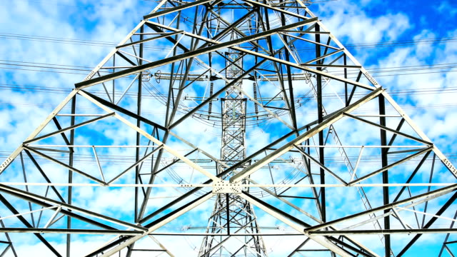 electricity high voltage power pylon against blue sky - sending stock videos and b-roll footage