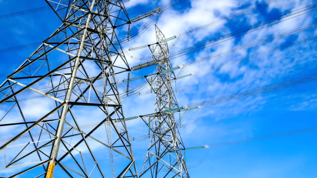 electricity high voltage power pylon against blue sky - high voltage stock videos and b-roll footage