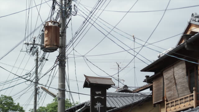 ms la electricity poles and roofs against sky, kyoto, japan - ワイヤー点の映像素材/bロール