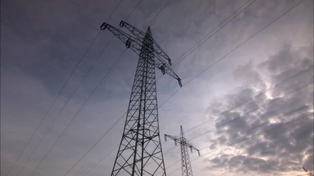 ws la electricity pylon against evening sky / kassel, germany - power line stock-videos und b-roll-filmmaterial