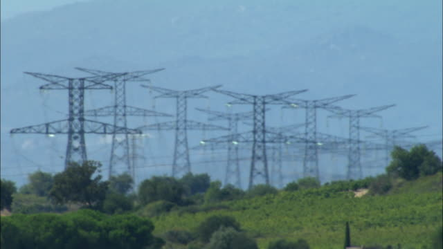 low aerial, electricity pylons on field, france - heat haze stock videos & royalty-free footage