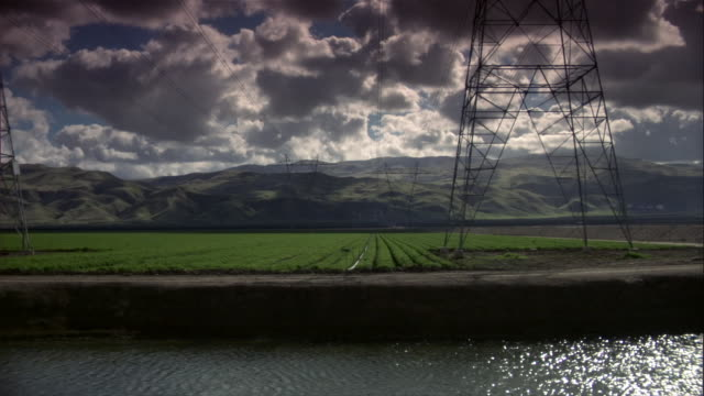 WS electricity pylons on fields at riverbank, California, USA