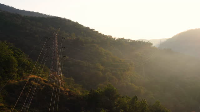 electricity pylons on hill with sunrise - sending stock videos & royalty-free footage