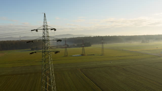 AERIAL Electricity pylons on the field