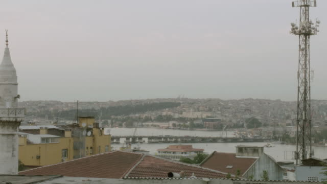 stockvideo's en b-roll-footage met pan electricity towers, rooftops, minarets, and dome of buildings and mosque overlooking the bosphorus strait / istanbul, turkey - torenspits