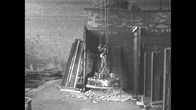 Electromagnet disc lowers on chain above pile of metal objects picks them up and moves toward camera brick wall in bkgd / Note exact year not known...