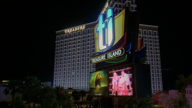 la ws electronic billboard in front of treasure island hotel and casino at night / las vegas, nevada, usa - 英字点の映像素材/bロール