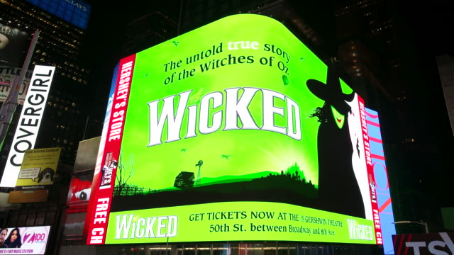 electronic billboard wicked broadway show advertisements in manhattan's times square at night broadway and 7th avenue new york city - broadway manhattan video stock e b–roll