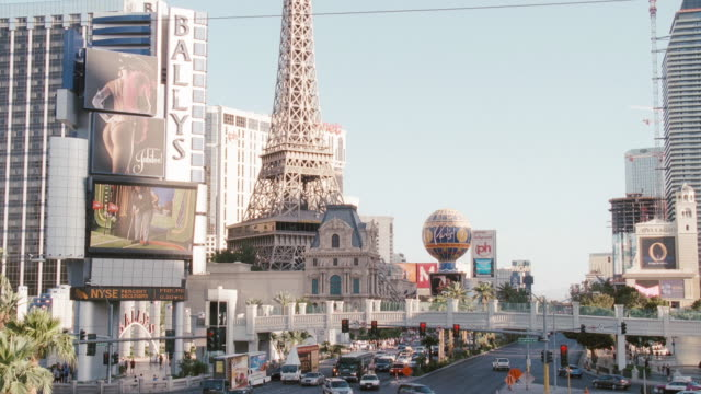 electronic billboards on bally's hotel and casino flash near a replica of the eiffel tower in las vegas, nevada. - replica eiffel tower stock videos & royalty-free footage