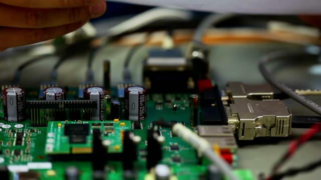 Electronic engineer testing circuit board