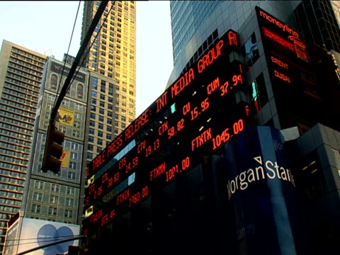 vídeos de stock, filmes e b-roll de electronic financial ticker tape sign moves along side of high rise office building new york city - estilo dos anos 2000