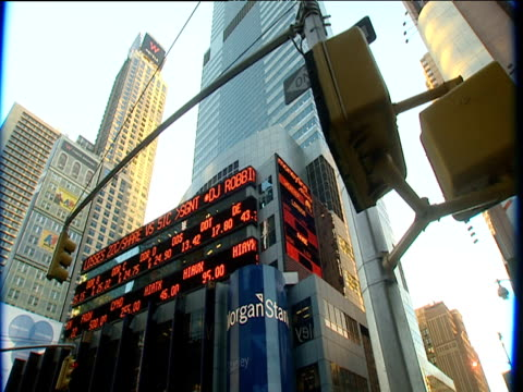 electronic financial ticker tape signs move on side of office high rise building next to traffic lights new york city - ticker tape stock videos and b-roll footage