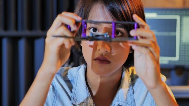 エレクトロニクスエンジニアはロボットと連携しています。若い女性は、学校のロボティクスクラブプロジェクトのための完全に機能するプログラマブルロボットに取り組んでいます。ワー� - プロトタイプ点の映像素材/bロール