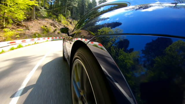 elegant and luxurious sports car driving on a winding mountain road on a beautiful sunny day - sports car stock videos & royalty-free footage