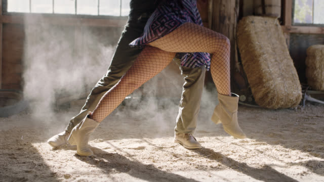 slo mo. elegant ballroom dancers kick up sawdust as they waltz in an abandoned barn. - collant video stock e b–roll
