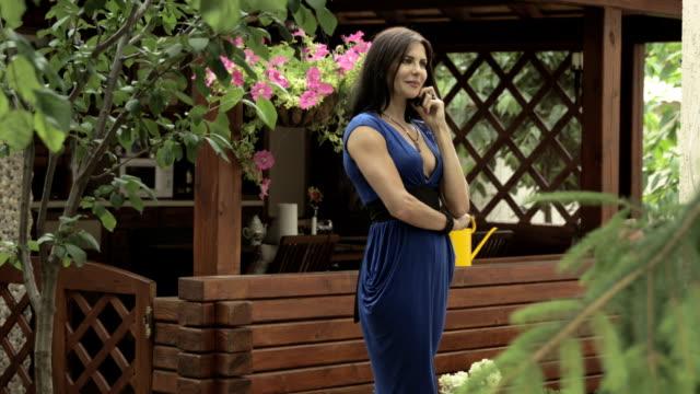Elegant brunette talks on phone standing near summer house