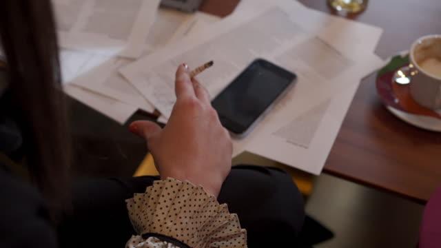elegante geschäftsfrau raucht während der arbeit in einem café - zigarette stock-videos und b-roll-filmmaterial