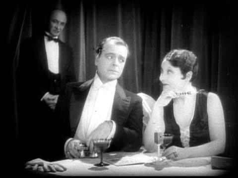 vídeos y material grabado en eventos de stock de ms, b&w, elegant couple at cafe table watching stage performance, 1920's  - boquilla producto relacionado con el tabaco