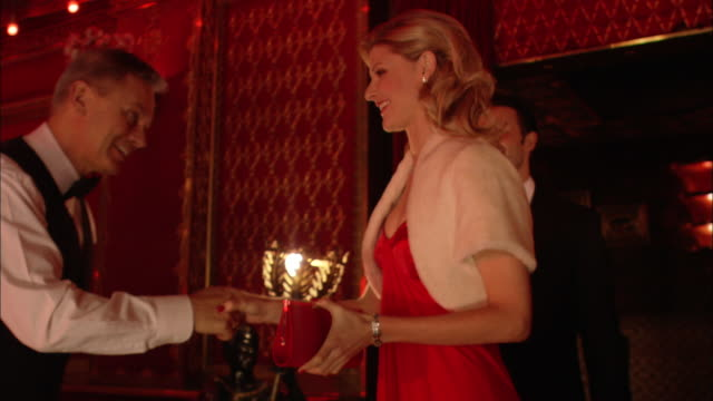 ms, pan, ws, elegant couple entering restaurant, violinist playing in background, london, england - お食事デート点の映像素材/bロール