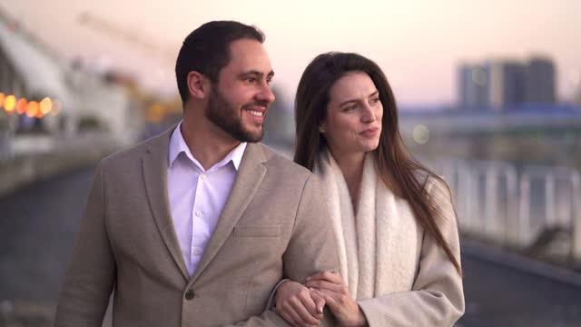 川のそばを歩くエレガントなカップル - お食事デート点の映像素材/bロール