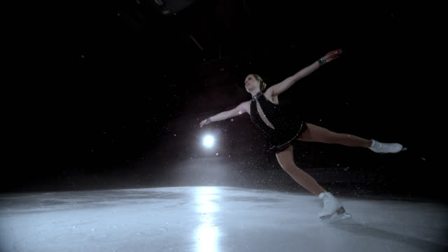 SLO MO DS Elegant female figure skater performing a jump