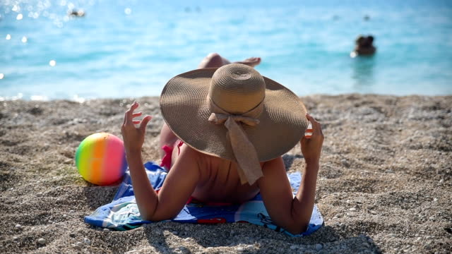 elegant female with summer hat on beach, rear view. - sun hat stock videos & royalty-free footage