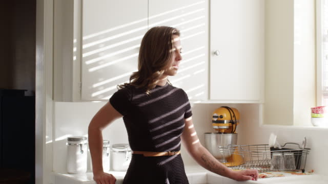 vidéos et rushes de elegant lesbian couple in the afternoon light in the kitchen - robinet