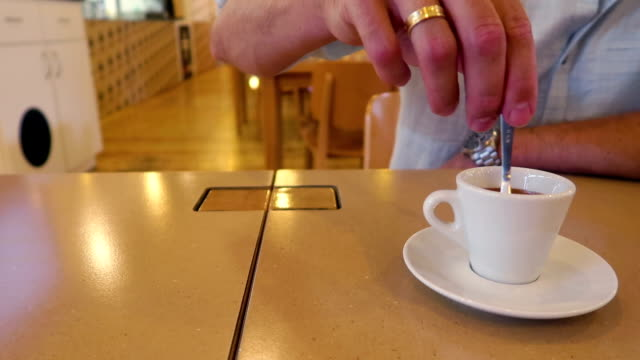 Elegant  man drink a cup of Italian coffee in cosy public place/ restaurant