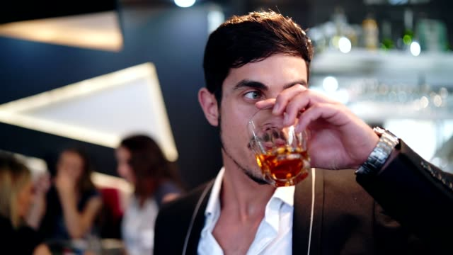 elegant man drinking whiskey in the bar - scotch whiskey stock videos and b-roll footage