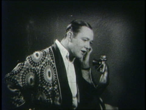 b/w 1927 elegant man (charles ray) in smoking jacket talking on telephone - stereotypically upper class stock videos & royalty-free footage