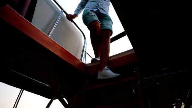 Elegant man is walking down the staircases into the yacht cabin