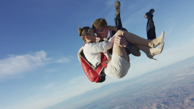 elegant skydiver with woman in his arms - fallschirm stock-videos und b-roll-filmmaterial