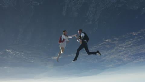 vidéos et rushes de elegant skydiving couple kisses hand - en l'air