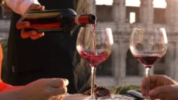 Elegant waiter serving pouring glass of red wine to romantic couple sitting at restaurant table in front of colosseum in rome at sunset