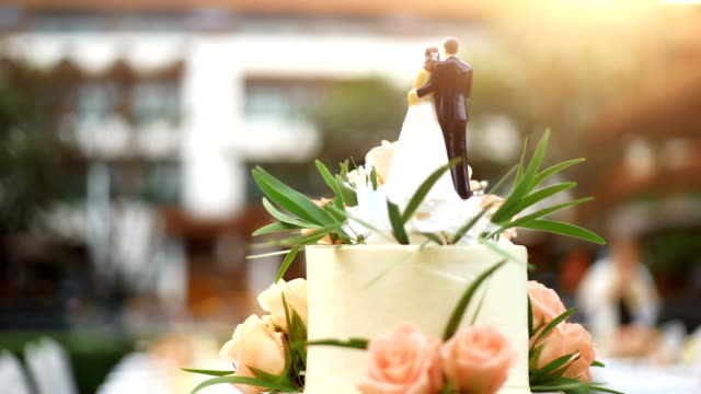 Elegant wedding cake with bride and groom figurines decorated with fresh flowers.