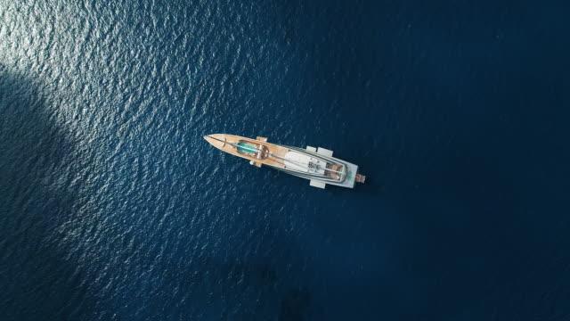 elegant vit yacht i medelhavet, nissi beach, ayia napa, cypern. antenn drönare sköt. - yacht bildbanksvideor och videomaterial från bakom kulisserna