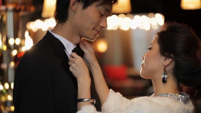 MS Elegant woman adjusting man's bow tie / China