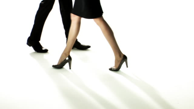 slo mo, cu, elegant woman and man walking in studio in different directions, low section - moving past stock videos & royalty-free footage