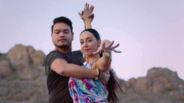 slo mo. elegant woman dances with partner and casts hand in front of camera in rocky desert terrain. - tango dance stock videos and b-roll footage