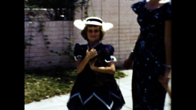 elegant woman in white hat walking toward the camera with two little girls in matching dress and hat; older girl holding black cat. - 黒猫点の映像素材/bロール