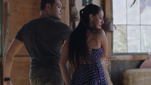 MED. Elegant woman kicks and performs passionate ballroom dance routine with partner in rustic desert barn.