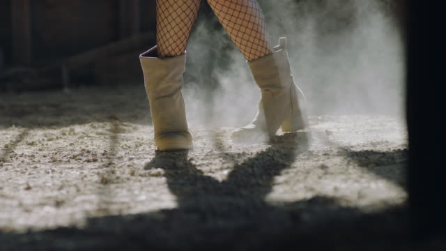 CU SLO MO. Elegant woman kicks up dust with boots as she dances and jumps on rustic barn floor.